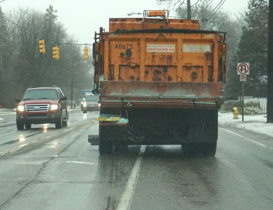 A Road Commission of Oakland County plow truck puts down some salt near downtown Birmingham.