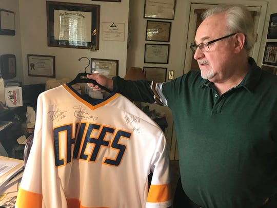 Binghamton's Frank Hamill holds up a Charlestown Chiefs jersey from the 1977 movie Slap Shot. Hamill, who played for the Broome Dusters from 1973-75, had a small role in the movie.