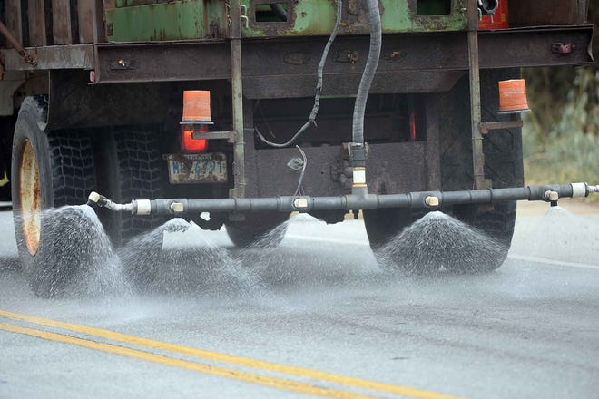 City workers spray brine on a bridge located near Crescent Ave. in Spartanburg on Feb. 25, 2015. Brine is a solution of salt (usually sodium chloride) in water that is used to combat freezing on roads.