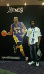Myles Sampson of Cocoa is pictured at an NBA All-Star game, near a poster of Los Angeles Lakers great Kobe Bryant.