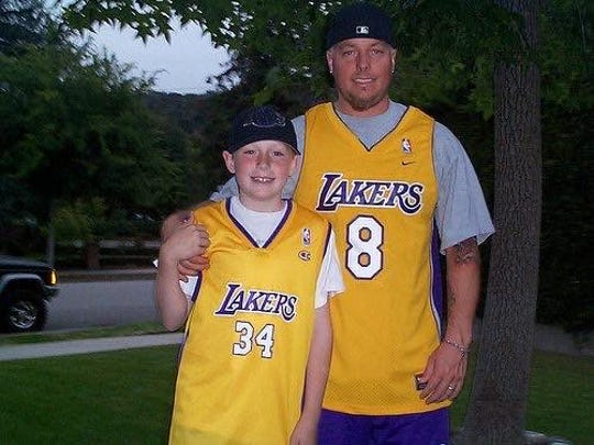 Longtime Lakers and Kobe Bryant fan Johnny Gaughan, right, is pictured with his son, Johnathan, in 2001.