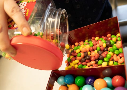 Anthony Collins tops off the skittles compartments of one of his vending machines on Jan. 31, 2020. Collins' passion for travel and technical skills go well with the vending business and has learned about the profit he can make.