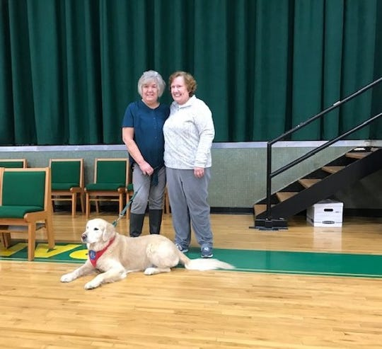 Mary Brown poses with Marilyn Gawelek and therapy dog Takeo.