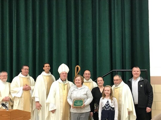 Brown poses with Bishop Robert Brennan and parish priests.
