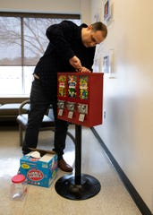 Anthony Collins locks the vending machines he just filled at the Pioneer Center on Main Street where his first machines were installed in Chillicothe, Ohio, on Jan. 31, 2020.  Collins started his own business AC Vending to pursue his passion even though he has a disability.