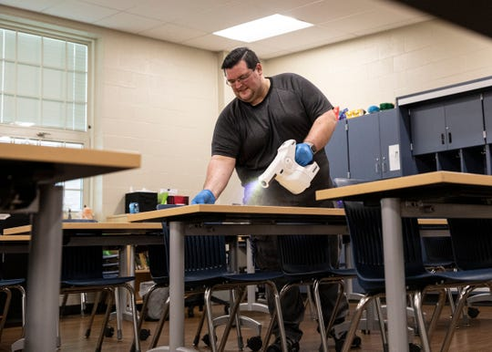 Chillicothe custodian Daniel Secoy uses a special gun with PURTABS sanitizing and disinfection tablets to spray down the desks and chairs of every room inside Chillicothe Intermediate School on Jan. 31, 2020, in Chillicothe. The school is scheduled to re-open on Tuesday after all the buildings had been disinfected twice.