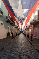 A giant Puerto Rico flag flies above Fortaleza Street in Old San Juan on Jan. 9, 2020.