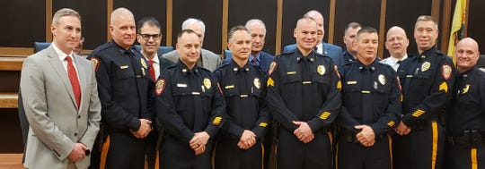 The newly promoted police officers with Mayor Matt Moench and the township council.