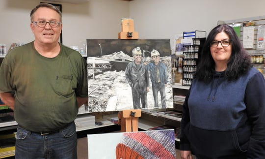 Sam Bennett and Carole Hunt pose with a portrait of Sam and his late father, Arthur, Hunt painted in front of a now closed min on Ohio 83 South. Arthur died in a mining accident in 1971 and is depicted in a statue on the Coshocton Court Square.