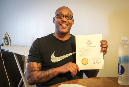 Moriando Moore of Des Moines holds a certificate of citizenship restoration signed by Iowa Gov. Kim Reynolds at his apartment on Thursday, Jan. 31, 2020. Moore, a convicted felon, said he's looking forward to voting for the first time in November.