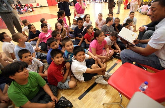 """Curtis Granderson reads """"Casey at the Bat"""" to students at Roberto Clemente Learning Academy in Detroit. on June 13, 2007. Granderson, Fernando Rodney and Neifi Perez visited students at Roberto Clemente School to boost reading and literacy as well as talk about teamwork."""