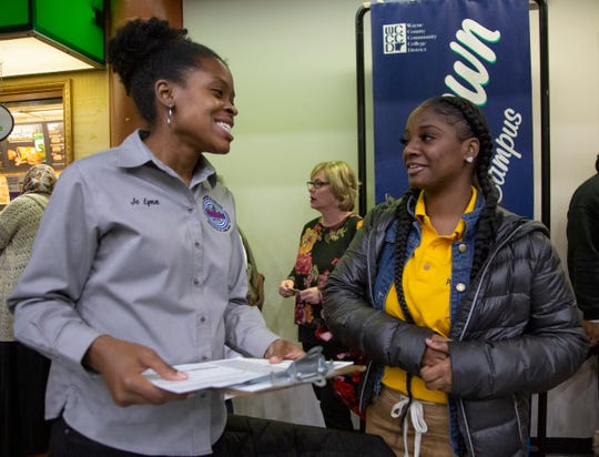 Principal Training Specialist Detroit Department of Elections Jo Lynn Williams, 32, of Oak Park left, helps Destiny Moore, 18, a student from East English Village high school register to vote during a census rally that was held for hundreds of metro Detroit high school students at the Wayne County Community College in Detroit Friday, Jan. 31, 2020.