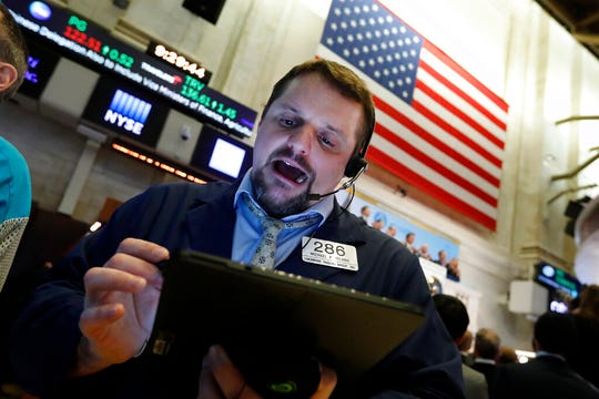 In this Jan. 9, 2020, file photo trader Michael Milano works on the floor of the New York Stock Exchange. The U.S. stock market opens at 9:30 a.m. EST on Friday, Jan. 31. (AP Photo/Richard Drew, File)