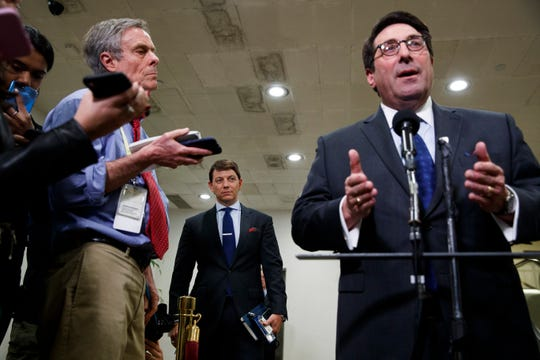 Deputy White House press secretary Hogan Gidley, center, listens as President Donald Trump's personal attorney Jay Sekulow, right, speaks to the media during a break in the impeachment trial of President Donald Trump on charges of abuse of power and obstruction of Congress, Friday, Jan. 24, 2020, on Capitol Hill in Washington.