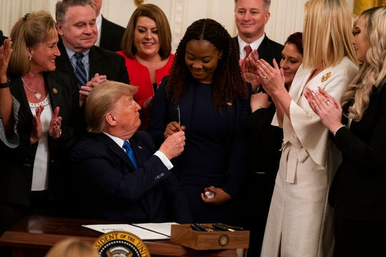 President Donald Trump hands a pen to survivor Bella Hounakey after signing an executive order to help combat human trafficking, in the East Room of the White House, Friday, Jan. 31, 2020, in Washington.