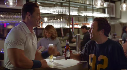 """This undated image provided by Michelob ULTRA shows John Cena, left, and Jimmy Fallon in a scene from the company's 2020 Super Bowl NFL football spot. Wrestler-turned-actor John Cena tries to convince Tonight Show host Jimmy Fallon that there's a """"lighter side"""" to working out, with cameos by Tonight show band The Roots and runner Usain Bolt."""