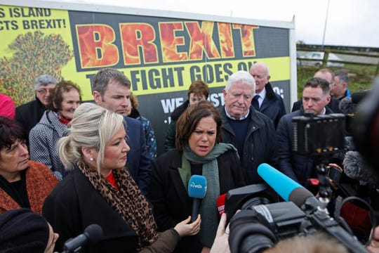 Sinn Fein leader Mary Lou McDonald, center, and deputy leader Michelle O'Neill, left, answer questions of journalists next to a sign rejecting Brexit, on the border of Northern Ireland and the Republic of Ireland, Friday.