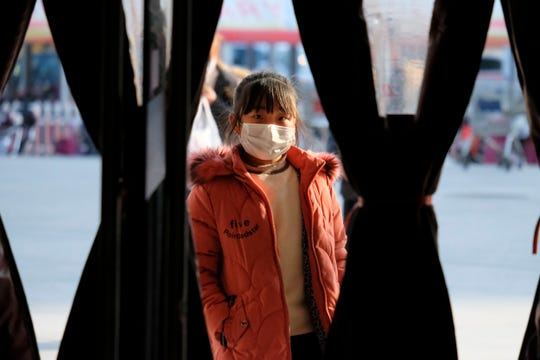 A girl wearing a face mask stands in the entrance to a shop in Wuhan in central China's Hubei Province, Friday.