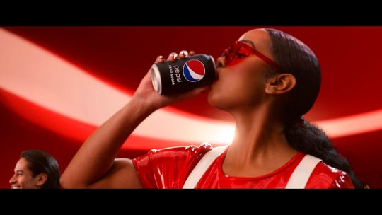 """This undated image provided by PepsiCo shows H.E.R. in a scene from the company's 2020 Super Bowl NFL football spot. Pepsi tries to reignite the Cola Wars with Missy Elliott and H.E.R. performing an updated version of """"Paint it Black"""" that starts with a red cola can that looks like a Coke changing into a black can of Pepsi Zero Sugar."""