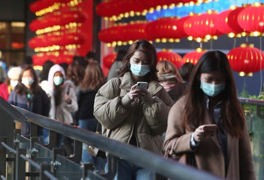 People wear face masks and walk at a shopping mall in Taipei, Taiwan on Friday.