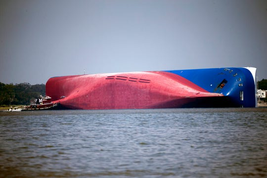 In this Sept. 9, 2019, file photo, a Moran tugboat nears the stern of the capsizing vessel Golden Ray as a tent and rescuers can be seen near the bottom of the ship near the tug boat in Jekyll Island, Ga. A Texas-based salvage company will cut up and remove the 656-foot (200- meter) shipwreck from St. Simons Sound off the coast of Georgia.