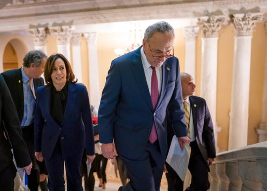 Senate Minority Leader Chuck Schumer, D-N.Y., joined by Sen. Kamala Harris, D-Calif., left, heads to speak to reporters to criticize the process in the Republican-controlled Senate Friday, Jan. 31, 2020.