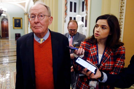 Sen. Lamar Alexander, R-Tenn., talks to reporters as he walks past the Senate chamber prior to the start of the impeachment trial of President Donald Trump at the U.S. Capitol Friday Jan 31, 2020.