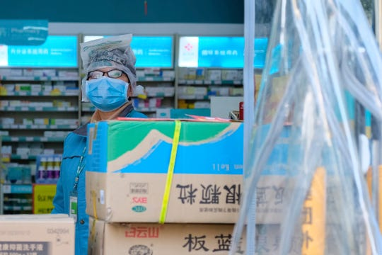 A clerk wearing a face mask and a plastic bag stands in a pharmacy in Wuhan in central China's Hubei Province, Friday.