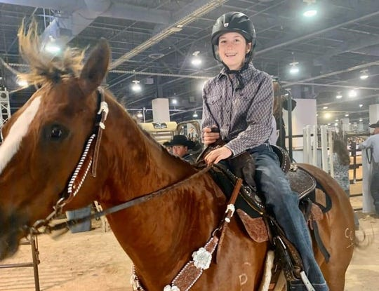 Madison Murphy poses for a photo with her horse after a recent competition.