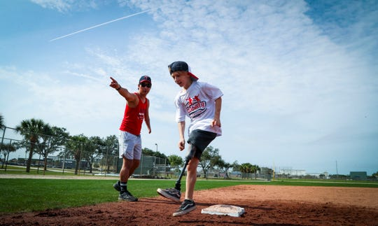 """Samuel Rudloff, from Missouri and volunteer coach, sends Dale """"Trip"""" Hyndman to home plate as the kids practice running bases.  Port Saint Lucie 9NubAbility Athletics Foundation is hosting the organization's winter baseball clinic for limb-different children in Fort Myers. The Minnesota Twins hosted the first day of activities at their spring training complex, Hammond Stadium.  The camp is open to children with congenital or traumatic loss of one or more limbs ages four to 17 who wish to improve their baseball or softball game."""