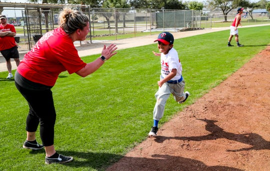 Hayden Thompson, of Texas and volunteer coach, high-fives a player running for home plate. NubAbility Athletics Foundation is hosting the organizationÕs winter baseball clinic for limb-different children in Fort Myers. The Minnesota Twins hosted the first day of activities at their spring training complex, Hammond Stadium.  The camp is open to children with congenital or traumatic loss of one or more limbs ages four to 17 who wish to improve their baseball or softball game.
