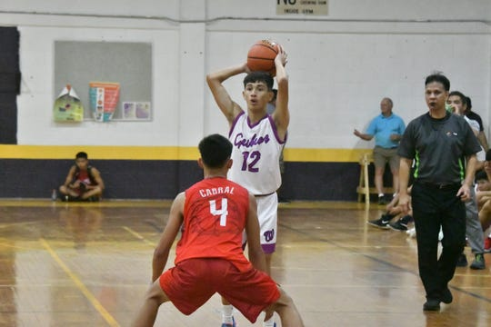 George Washington High's  Jay Ogo looks for an open teammate while being defended by Okkodo High's Kevin Cabral during their Guam Interscholastic Sports Association Boys Basketball game Jan. 30 at the GW gym.