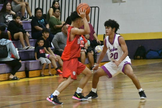 Okkodo High guard Kevin Cabral, left, is defended by GW High's  Joshua Sebastian during their Interscholastic Sports Association Boys Basketball game Jan. 30 at the GW gym.