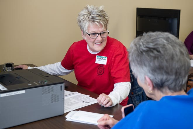 Henderson volunteer Ylonda Nall helps a local woman with her tax documents.