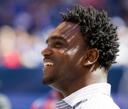 Edgerrin James smiles as he watches video highlights of his career, before being inducted into the Ring of Honor for the Indianapolis Colts at Lucas Oil Stadium in 2012.