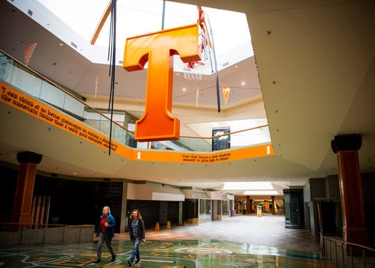 Sisters Rachel McKinney, left, and Suzy Sutton walk under the hanging Power T toward the former J.C. Penney inside a mostly empty Knoxville Center Mall, formerly known as East Towne Mall, on its final day on Friday, January 31, 2020.