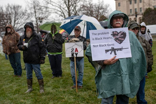 Gun supporters hold signs as they brave the rain during a Second Amendment rally at the Capitol building in Frankfort, Ky on Friday. Jan. 31, 2020