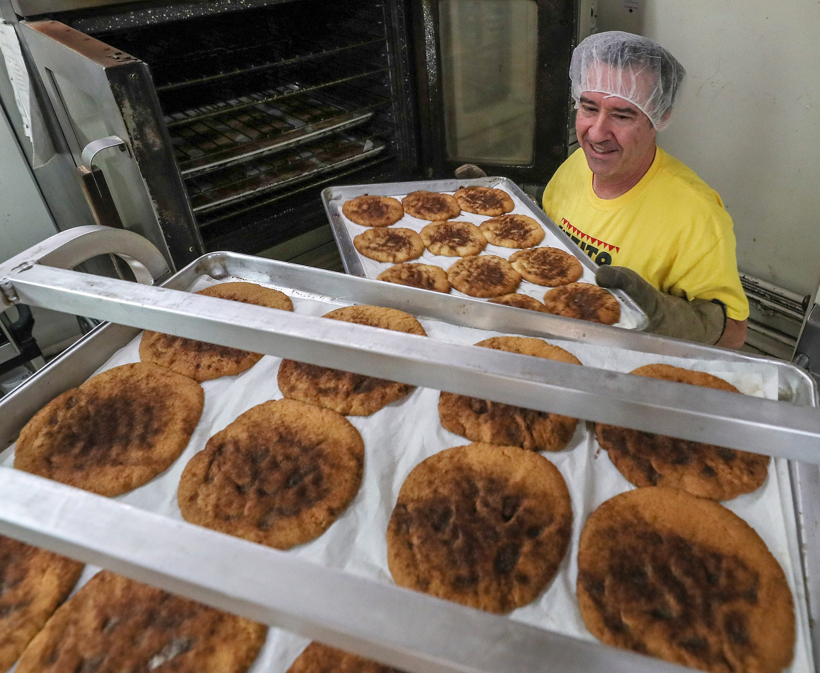 5:12 AMTodd Bartlett, husband of Elizabeth Kizito, takes a tray of the famous cookies out of the oven at the store on Bardstown Road in the Highlands on Jan. 31, 2020.