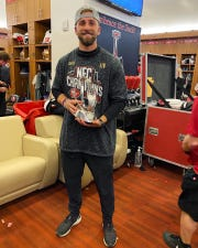 Atticus Bohr, 22, of Okemos is a full time equipment manager intern with the San Francisco 49ers. Bohr poses with the NFC Championship George Halas Trophy after the 49ers' 37-20 win over Green Bay.