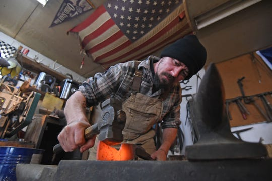 """Dustin Parrella hammers hot metal in his garage Friday afternoon. Parrella will be on """"Forged in Fire"""" Wednesday on the History Channel."""