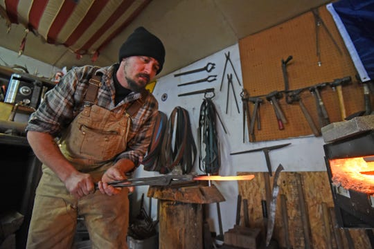 Dustin Parrella takes hot metal out of the furnace before shaping.