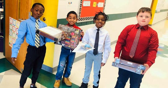McKinley Elementary students and new Boys with a Purpose club members, (left to right) Victor Wilson, Jayden Thompson, Shamoz Moore and Garrett Bruglar, deliver rewards to fellow students. The new club is an initiative to help boys at McKinley learn about leadership, kindness and respect.