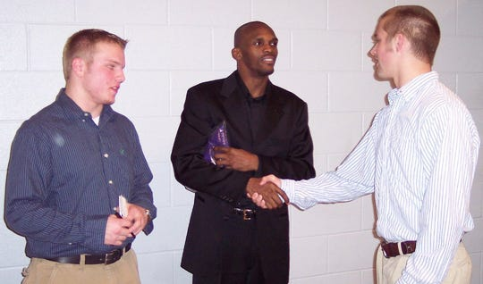 Feb. 2, 2006 - St. Louis Rams wide receiver Isaac Bruce shakes hands with DeSoto Central's Kris Armstrong at Thursday's football awards ceremony. Armstrong and John Hill are invited walk-ons at the University of Memphis, the same school Bruce shined at before moving on to the NFL.