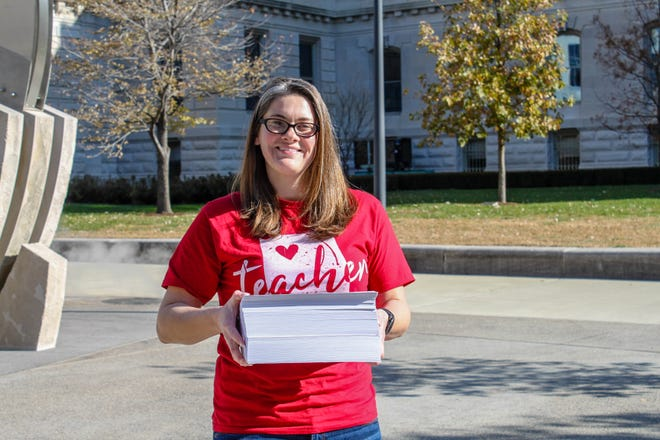 Teacher Brittany Kloer, a candidate for state representative, holds 1,269 pages of new Indiana education law enacted by the General Assembly in 2019.