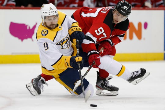 New Jersey Devils left wing Nikita Gusev (97) and Nashville Predators left wing Filip Forsberg (9) go after the puck as Forsberg falls to the ice during the second period on Thursday, Jan. 30, 2020, in Newark, N.J.