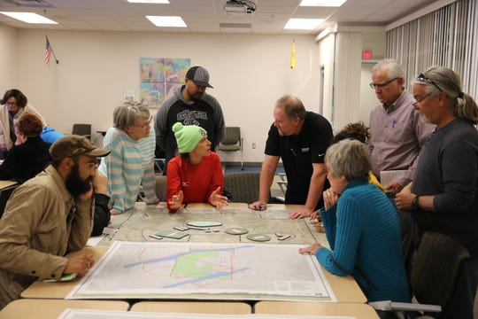 Attendees lay out where they'd ideally like elements to go in the new East Mesa Public Recreation Complex to project manager Wesley Hall, in black.