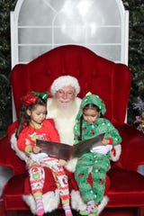 Santa (aka Greg Scarboro) enjoys storytime with Sophia, right, and Elena at Mesilla Valley Mall in 2019.