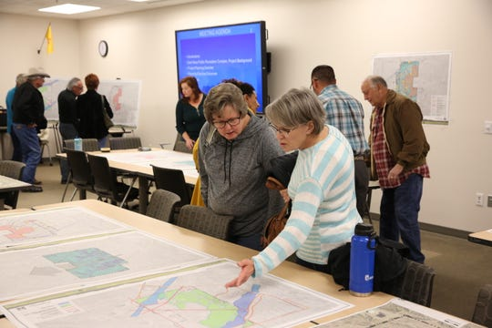 Carol Ezell, from left, and Kathy Tarazoff view maps of the land where the East Mesa Public Recreation Complex will be built at a public meeting Jan. 30, 2020.