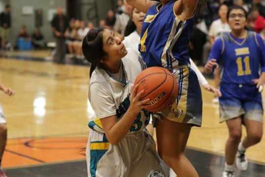 Navajo Prep's Tia Morgan goes in for the and-one basket against Zuni during Thursday's District 1-3A girls basketball game at the Eagles Nest in Farmington.
