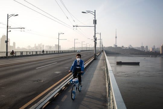 WUHAN, CHINA - JANUARY 31:  (CHINA OUT) A man wears a protective mask as he rides a bicycle across the Yangtze River Bridge on January 31, 2020 in Wuhan, China.  World Health Organization (WHO) Director-General Tedros Adhanom Ghebreyesus said on January 30 that the novel coronavirus outbreak has become a Public Health Emergency of International Concern (PHEIC).  (Photo by Stringer/Getty Images)